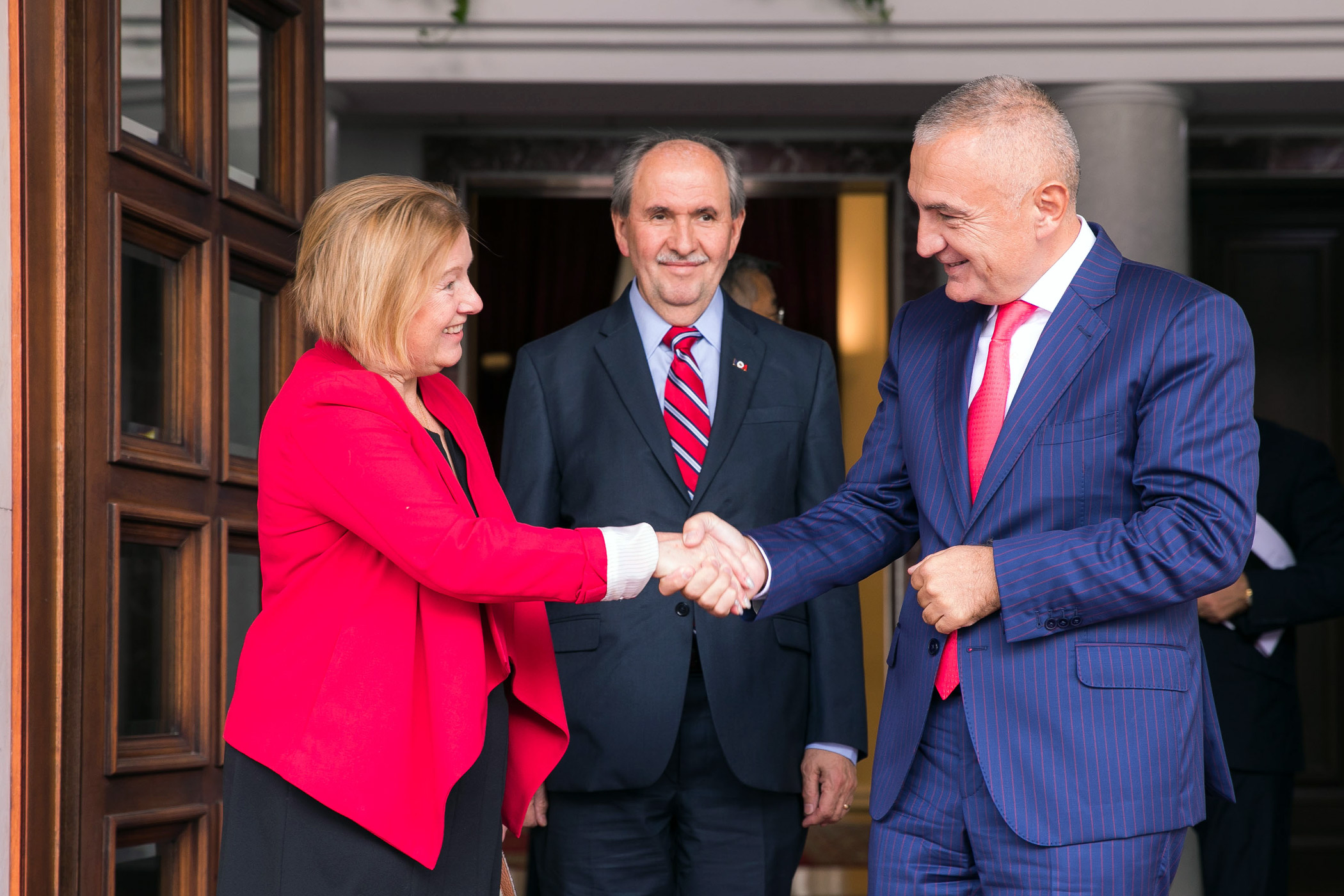 A woman shakes the hand of a man while a third person stands between them