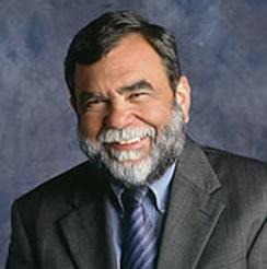 Formal portrait of an older bearded man in a grey suit