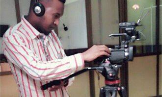 man works on camera on a tripod