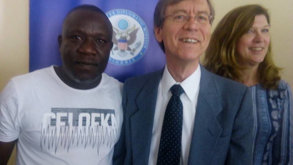 An African man in a t-shirt stands next to a white man in a suit and a white woman smiles in the background