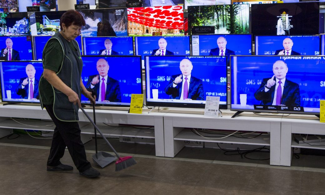 A cleaner walks past TV sets showing Russian President Vladimir Putin during his annual live call-in show in a shop in Moscow, Russia,