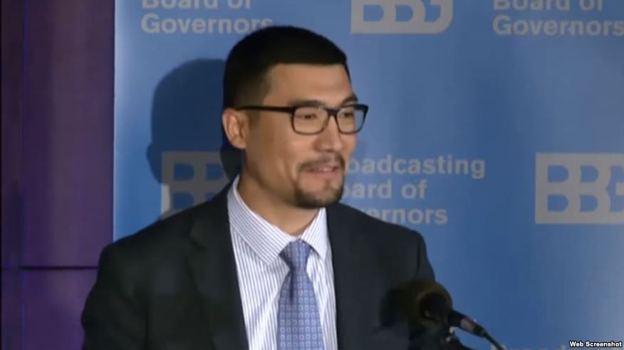 Asian man in a suit speaks in front of a blue background