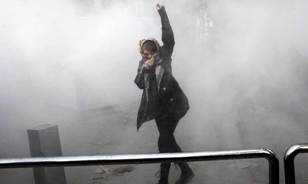 woman with hand held high, surrounded by smoke