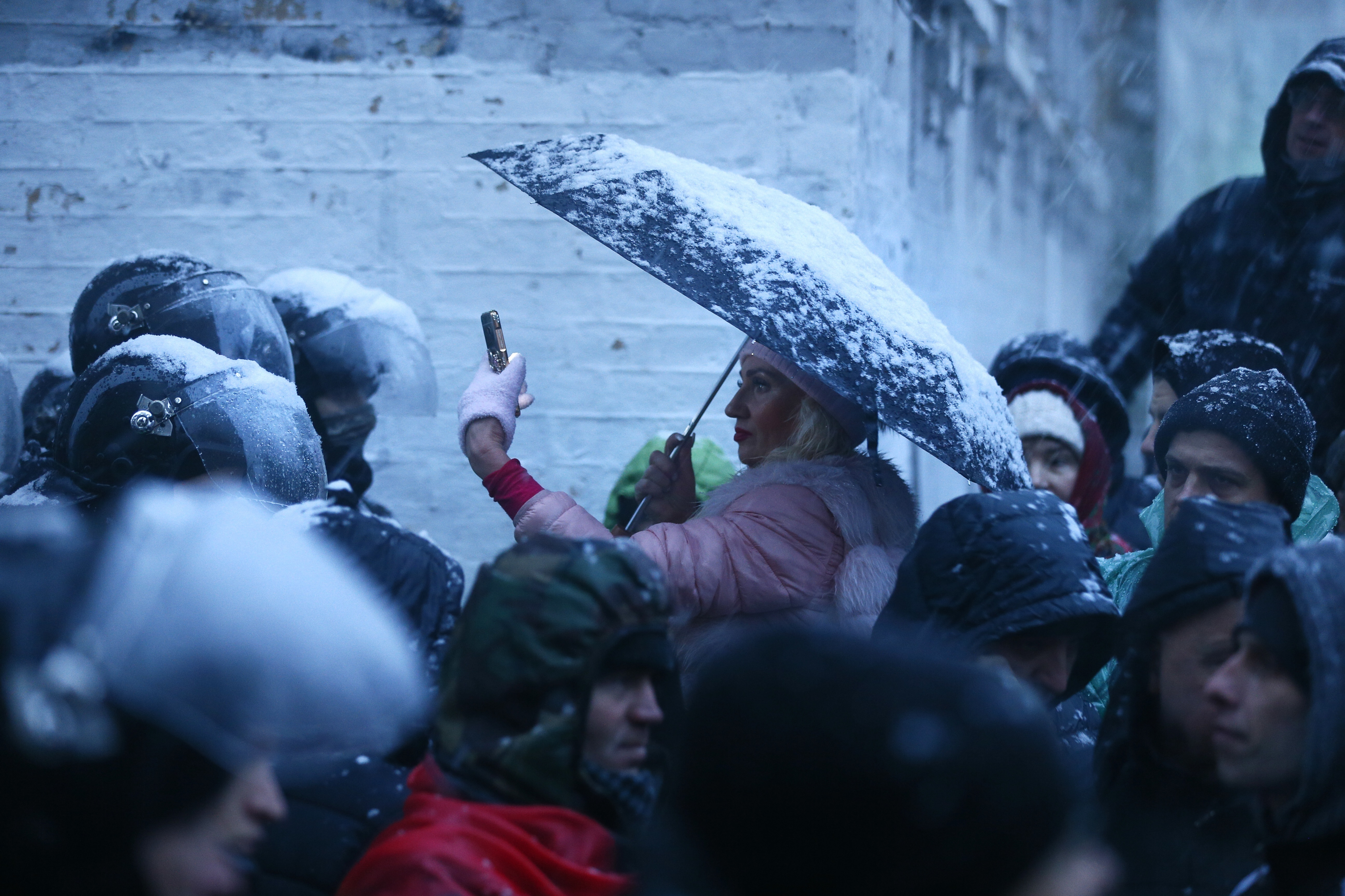 woman under a snowy umbrella takes a photo with her cell phone of a police blockade