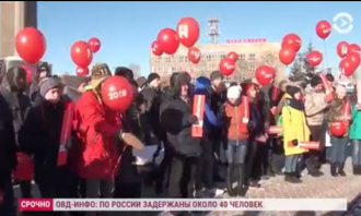crowd of protestors outside holding red ballons