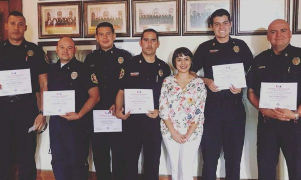 group of 6 men in uniform and a woman, all smiling at camera, holding certificates