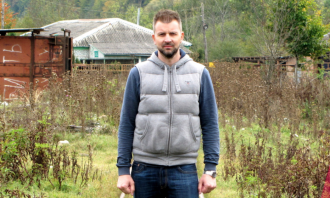 man outside standing between old train tracks