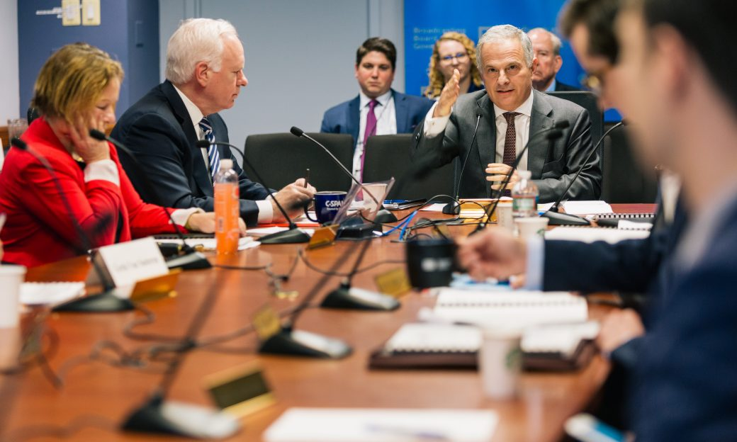 two men at a board table, one is talking. Other people are in the room looking on.