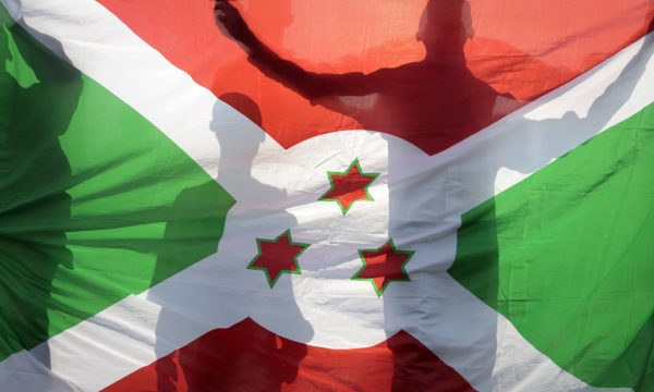 three people are silhouetted behind the Burundi national flag