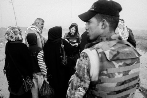 a woman wearing a press flak jacket listens to people who have surrounded her