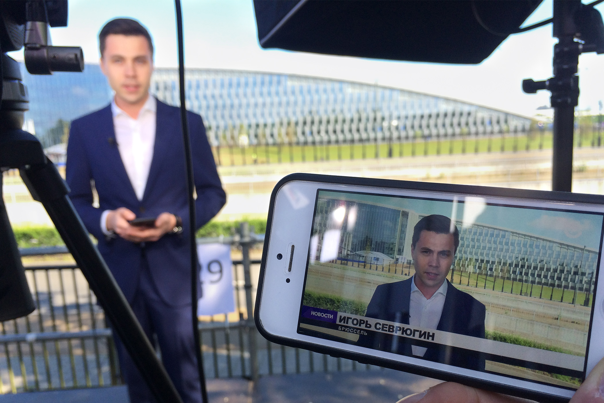 A mobile phone shows a reporter outdoors, the broadcast setup is out of focus in the background
