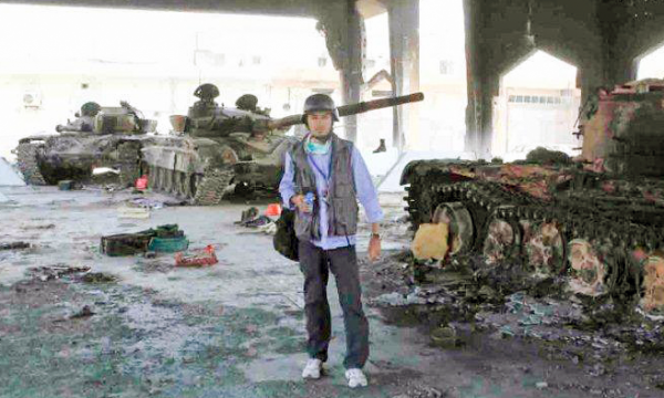 A reporter in tactical gear stands next to a burned out tank with two others in the background