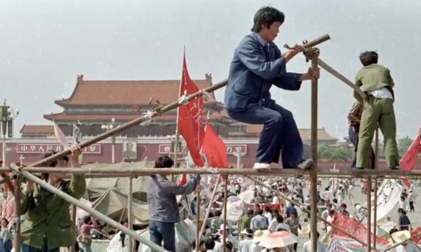 Photo of protesters climbing scaffolding at the 1989 Tiananmen Square protest.