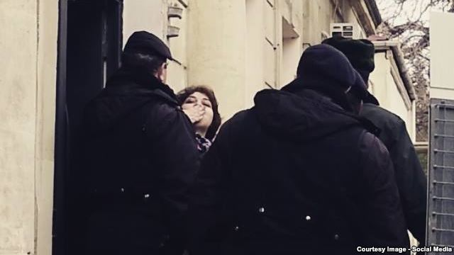 Khadija Ismayilova tries to greet supporters and journalists outside the Baku courtroom on Januarya 27, when she had her pretrial detention extended.