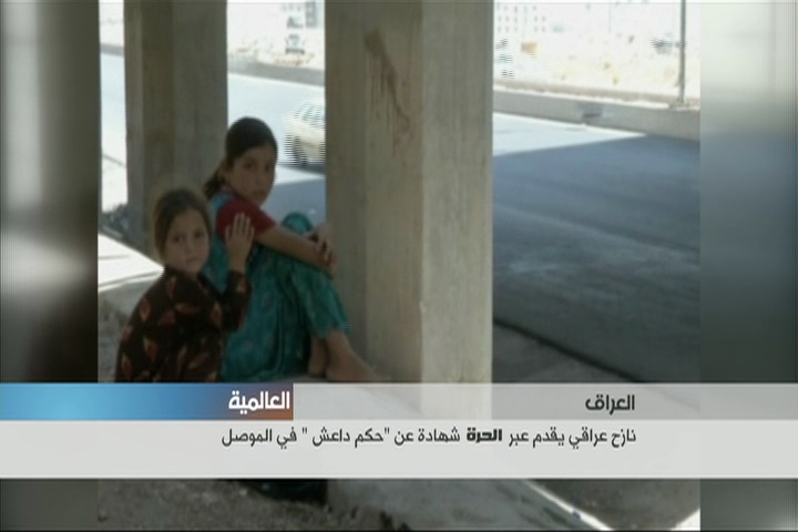 two young girls sit on the ground in Mosul.