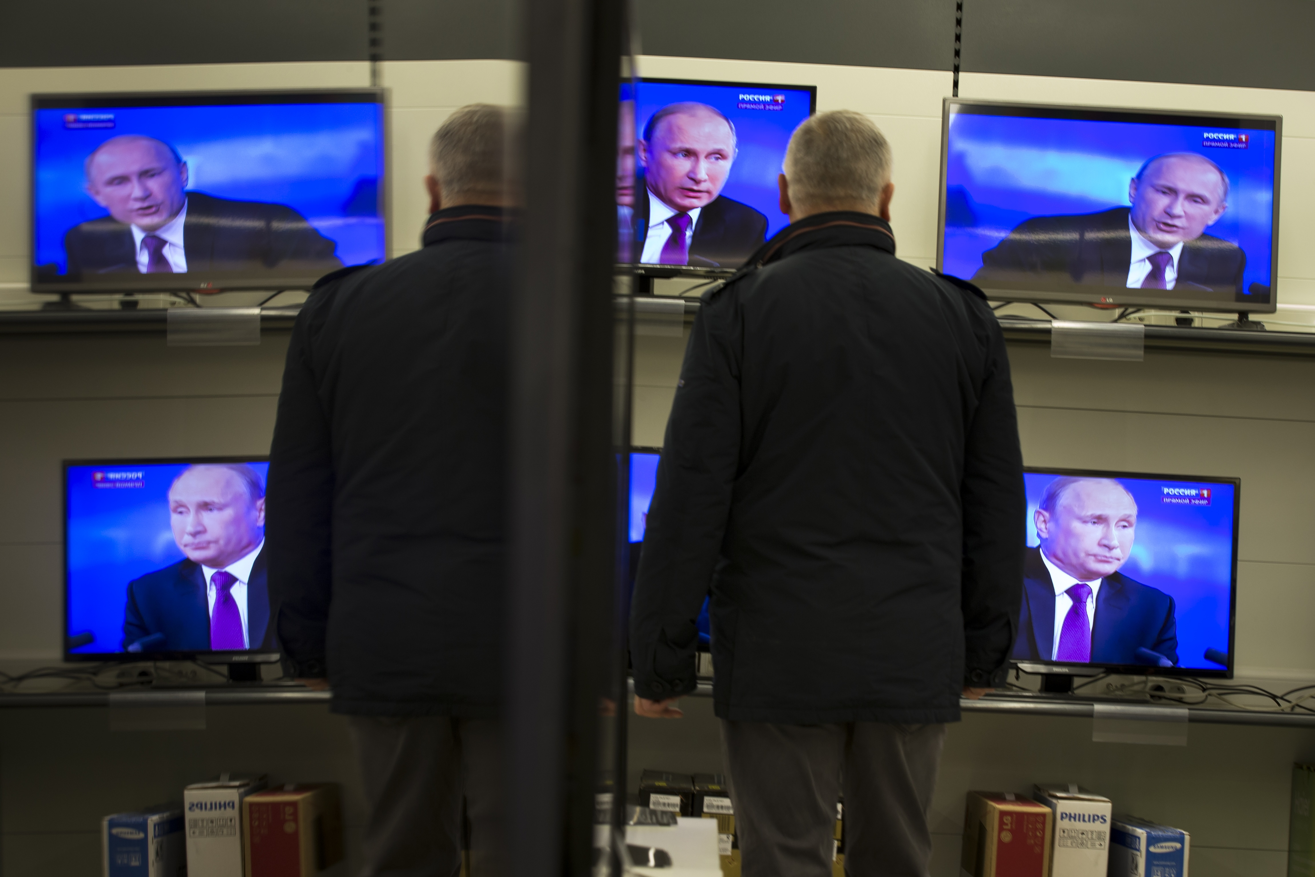 A man watches Russian President Vladimir Putin on TV screens in an electronic hypermarket in Moscow, Russia. (AP Photo/Alexander Zemlianichenko)