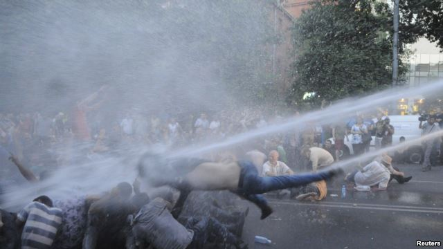 Protestors being knocked down by a jet of water.