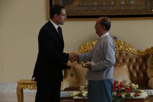 Two men shaking hands, one in a western style suit, the other in traditional Burmese clothes.