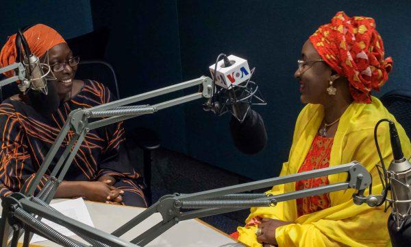 two women sit in a VOA radio studio
