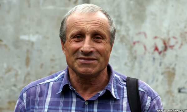 Portrait of a middle-aged man in front of a dirty wall