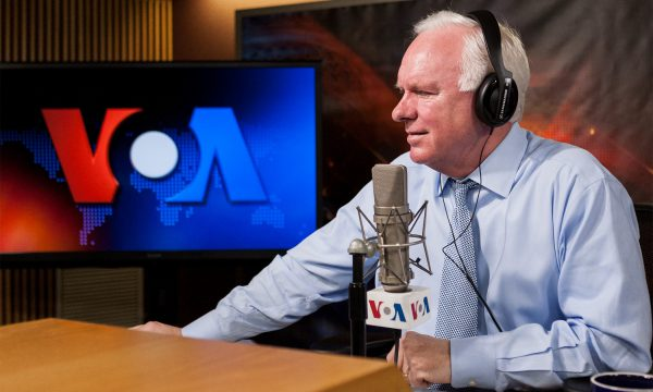 A man in a collared shirt and tie sits in front of a radio microphone with a VOA screen behind him.