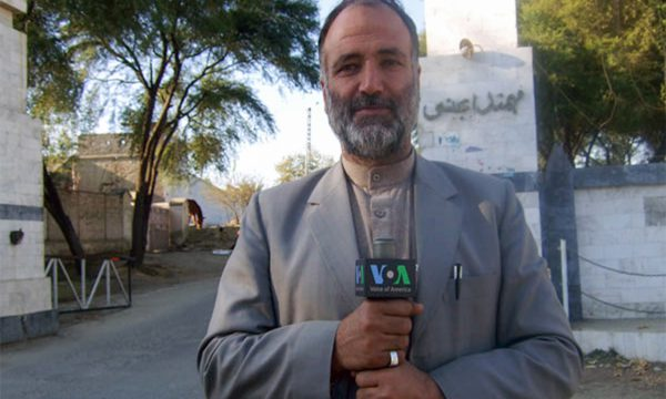 A man holding a VOA microphone stands on a street in front of a tree and a sign written in Arabic text