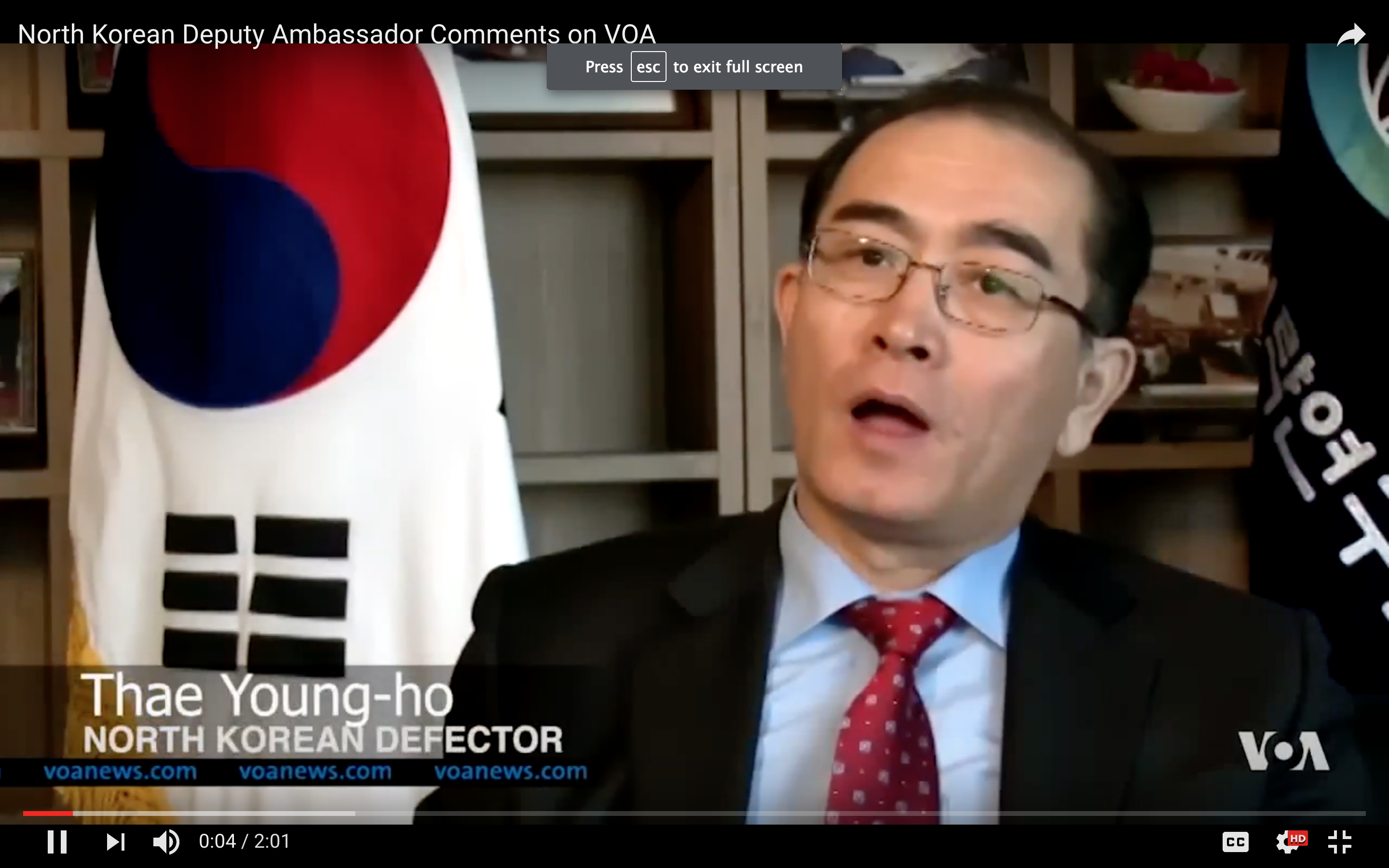 Man in suit with Korean flag behind him
