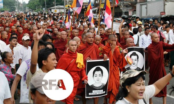 monks in red robes march in protest