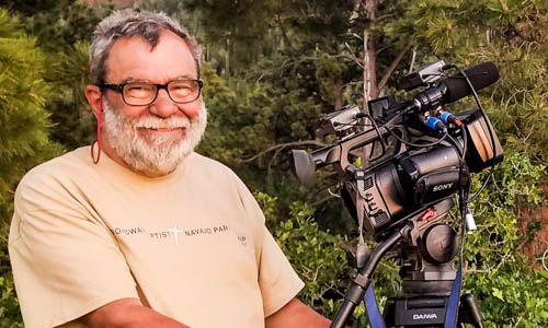 An older bearded man in a t-shirt stands next to a video camera on a tripod outdoors