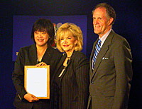 three people smile at camera, one holding a plaque