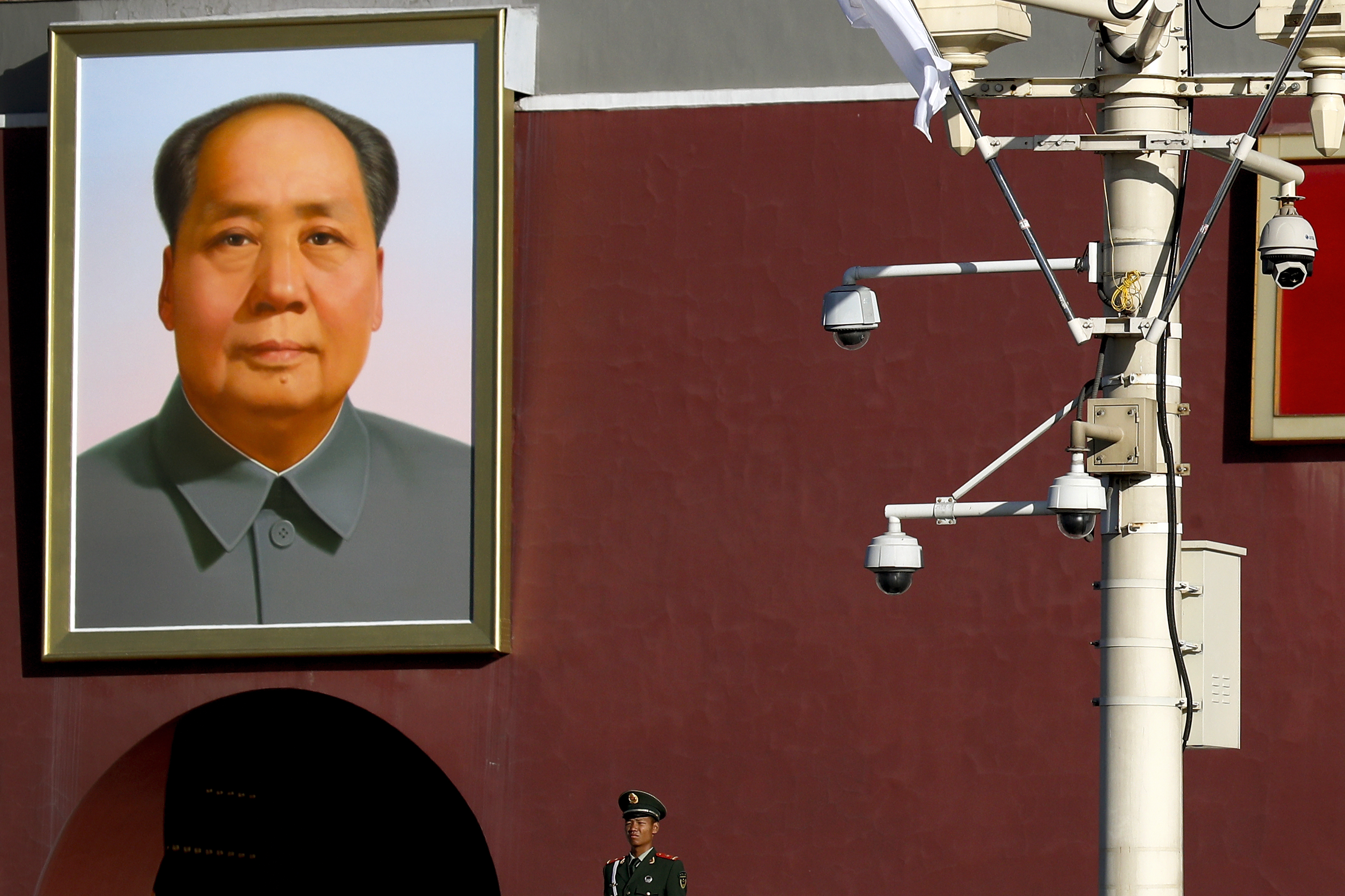 a pole with multipul surveillance cameras in front of a framed portrait of Chairman Mao on a red wall