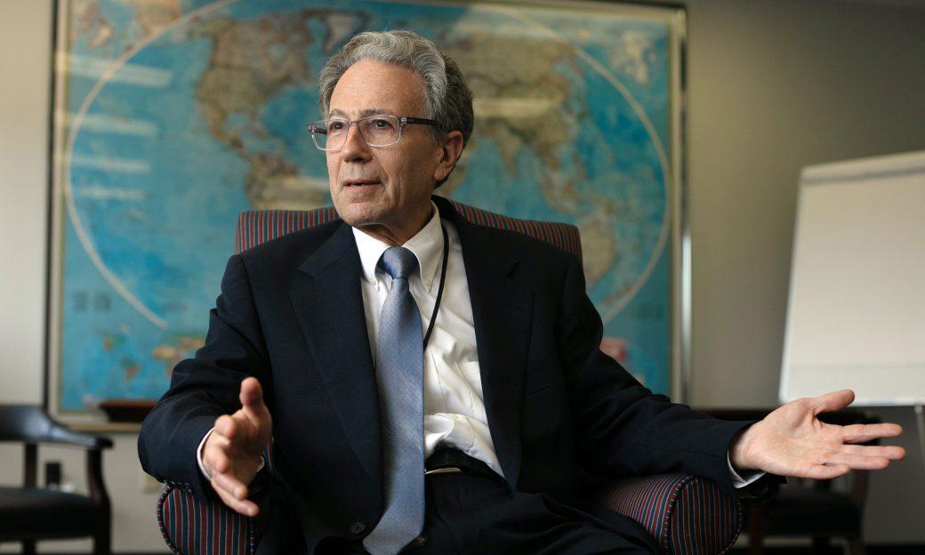 man in suit in an office talking