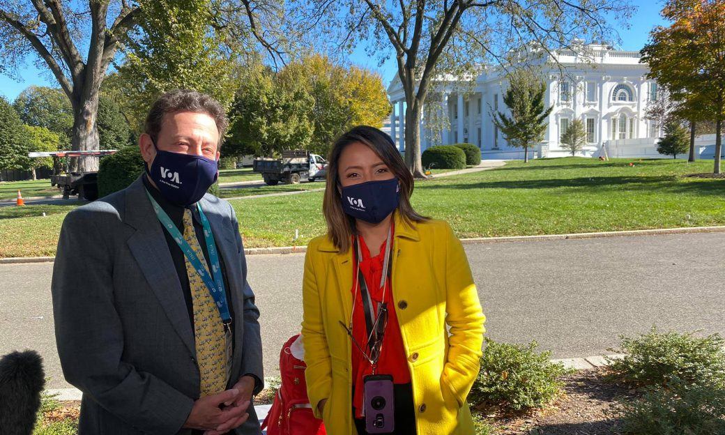 man and woman wearing masks in front of White House