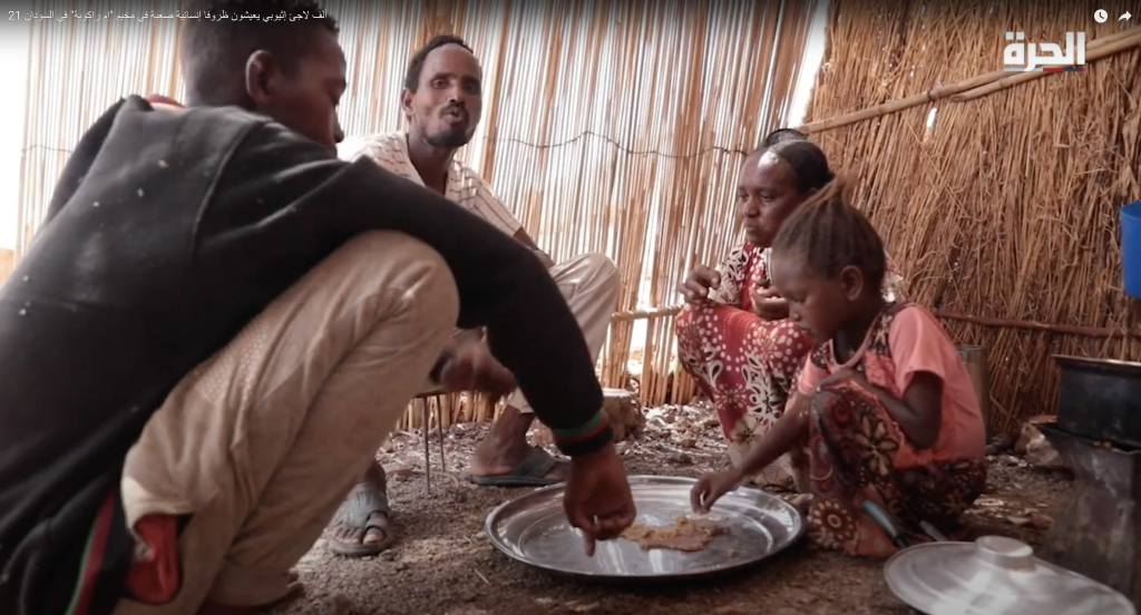 family of four sitting around a plate on the floor