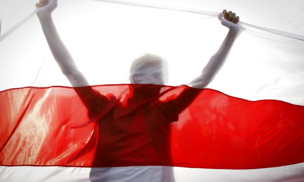 red and white flag held up by a person