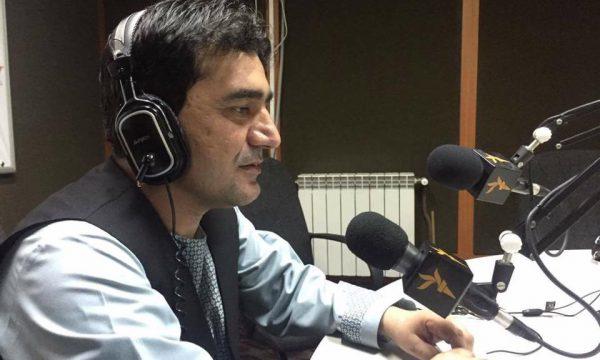 man in radio studio speaking into mic wearing headphones